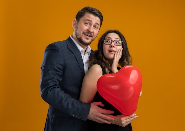 Happy and beautiful couple man and woman with red balloon in heart shape embracing celebrating valentines day over orange wall