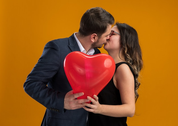 Happy and beautiful couple man and woman with red balloon in heart shape embracing and kissing celebrating valentines day over orange wall