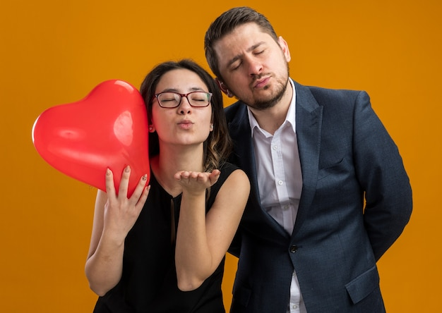 Happy and beautiful couple man and woman with red balloon in heart shape having fun blowing a kiss celebrating valentines day over orange wall
