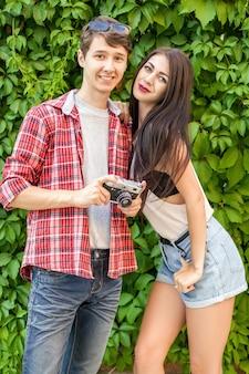 カメラとカジュアルなスタイルで緑の壁の近くの幸せな美しいカップル。 。