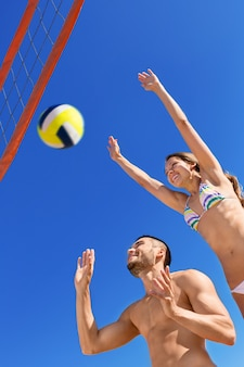 Happy beautiful couple playing volleyball