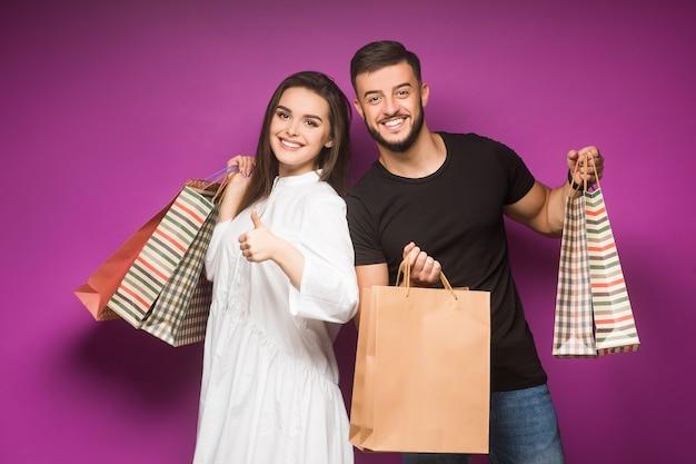 Felice bella coppia in posa con le borse della spesa su viola