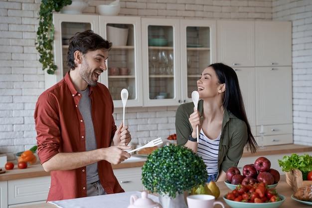 幸せな美しいカップルが笑って楽しんで自宅のモダンなキッチンで健康的な料理を準備します。