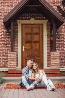 新しい家の前の毛布のカーペットに座っている幸せな美しいカップル