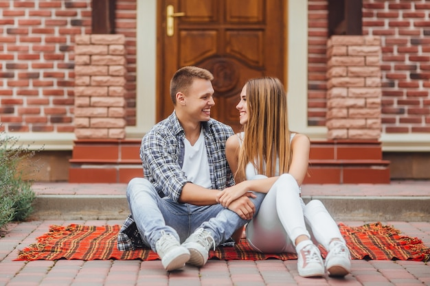 Happy beautiful couple sitting at the blanket  carpet in front of the new home.