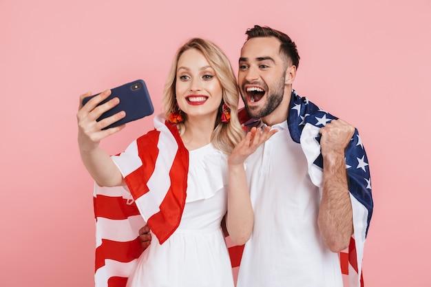 핑크색 위에 고립된 채 미국 국기를 들고 축하하고 셀카를 찍는 행복한 아름다운 커플