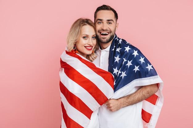 핑크색 위에 고립된 채 미국 국기를 들고 축하하는 행복한 아름다운 커플