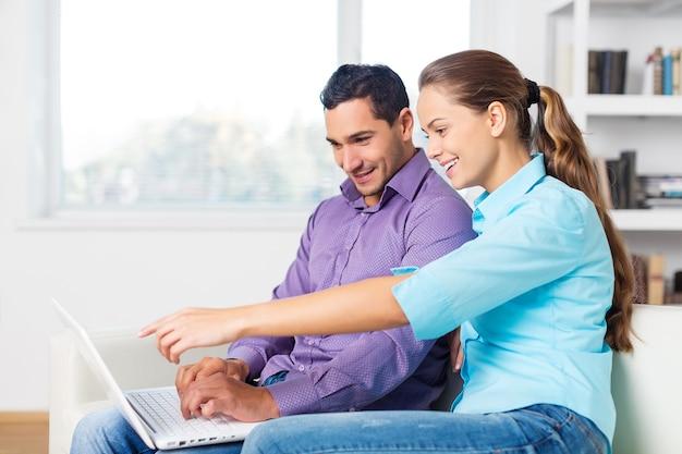노트북을 함께 사용하는 행복한 아름다운 커플