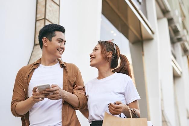スマートフォンを使用して一緒に買い物をして幸せな美しいカップル。