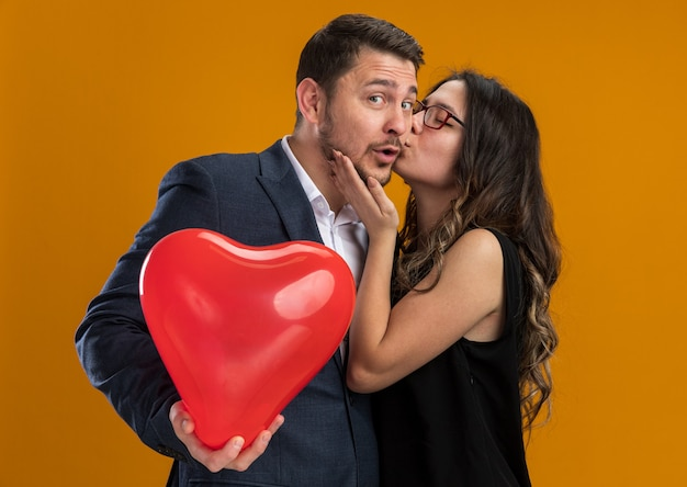 Happy and beautiful couple woman kissing her boyfriend with red balloon in heart shape celebrating valentines day over orange wall