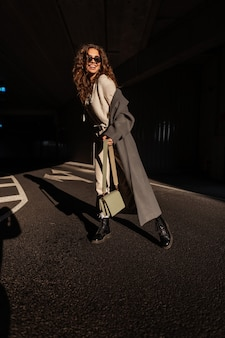 도시의 햇빛과 그늘에서 세련된 핸드백을 들고 세련된 긴 코트에 선글라스를 끼고 미소를 짓고 있는 행복한 곱슬머리 소녀. 캐주얼 도시 스타일 야외에서 재미 있는 여자