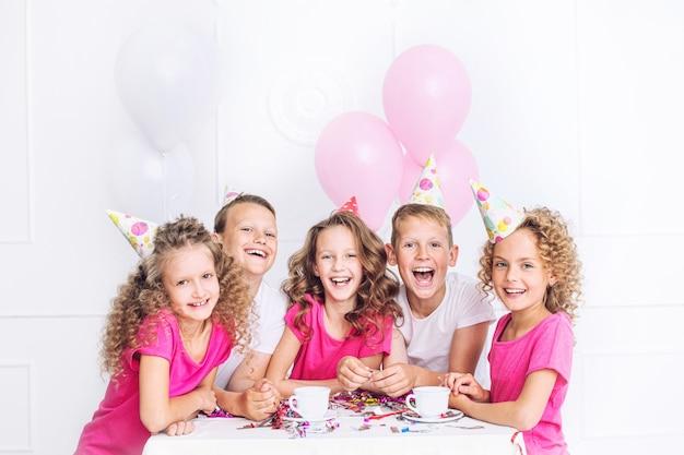 행복 한 아름 다운 귀여운 아이 화이트 룸의 테이블에 풍선과 색종이 함께 휴가 파티에서 미소
