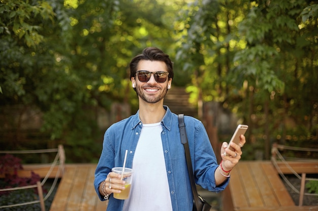 白いtシャツと青いシャツを着て、元気に見て、携帯電話を手に持って、サングラスで幸せな美しい黒髪の男性