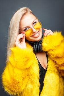 Счастливая красивая девушка ди-джея с улыбкой в модных солнцезащитных очках в стильной желтой шубе на сером