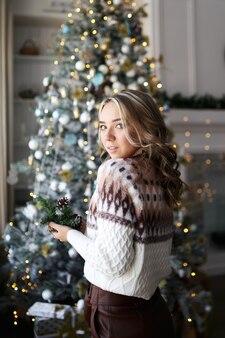 Счастливая красивая мечтающая женщина в теплом свитере возле шикарной елки дома