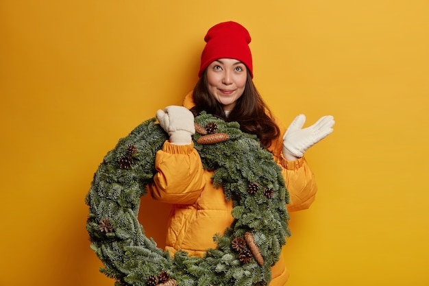 Happy beautiful ethnic woman looks thoughtfully above, wears red hat, warm coat and white mittens, carries green spruce wreath, thinks above celebrating christmas