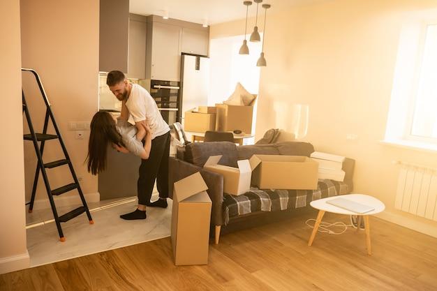 Счастливая красивая европейская пара танцует дома. концепция переезда в новую квартиру. идея молодой семьи. картонные коробки с вещами. интерьер современной однокомнатной квартиры. солнечный день