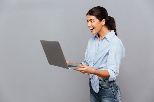 Happy beautiful excited woman using laptop isolated on a gray wall