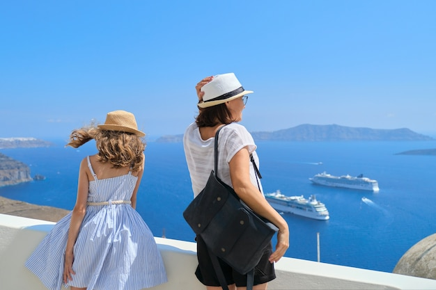 Happy beautiful family, mother and little daughter traveling together in mediterranean, greece, santorini island. beautiful scenic landscape with cruise liners background