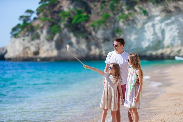 Счастливая красивая семья папы и детей на белом пляже