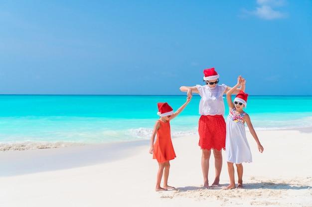 크리스마스를 축하하는 열 대 해변에서 빨간 산타 모자에 엄마와 아이들의 행복한 아름다운 가족