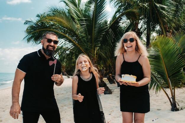 Счастливая красивая семья на тропическом пляже празднует рождение дочери. семья отмечает день рождения на острове маврикий.