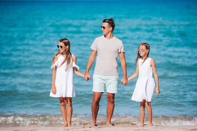 熱帯のビーチでの休暇で幸せな美しい家族