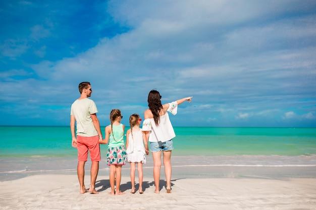ビーチで幸せな美しい家族。カリブ海の両親と子供たちの背面図