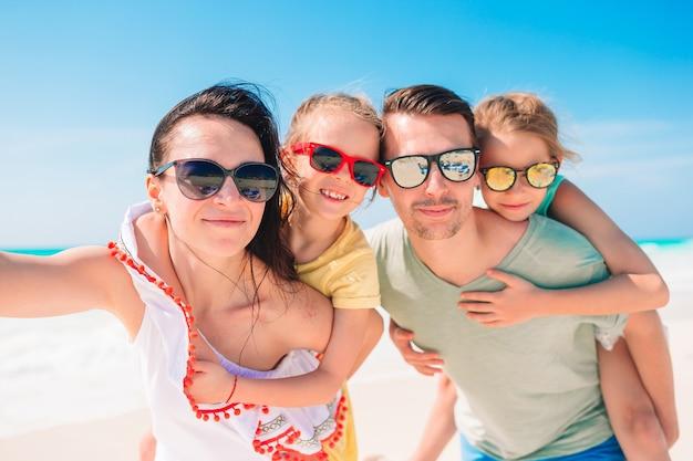 Счастливая красивая семья на белом пляже, с удовольствием