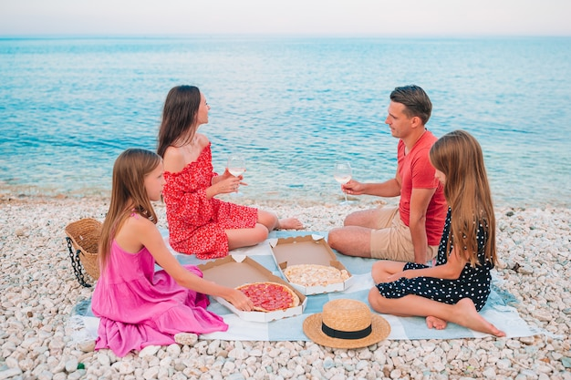 Happy beautiful family on a tropical beach having picnic together on the sunset
