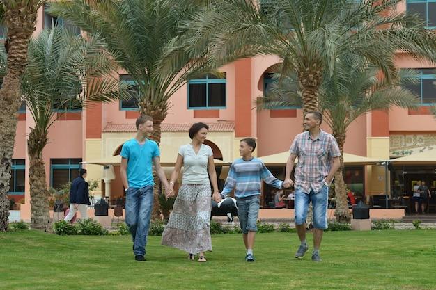 Счастливая красивая семейная прогулка в тропическом парке