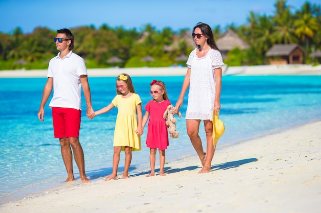 Happy beautiful family on white beach during summer vacation