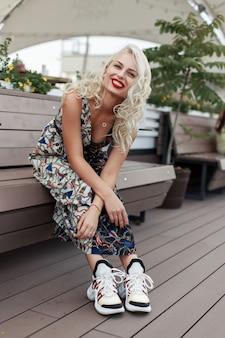 スタイリッシュなドレスを着て笑顔で幸せな美しいファッションモデルの女性がベンチに座って、瞬間を楽しんでいます
