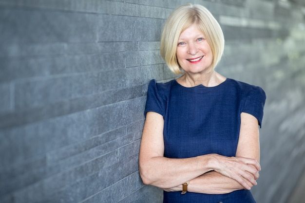 Happy beautiful female executive leaning on wall