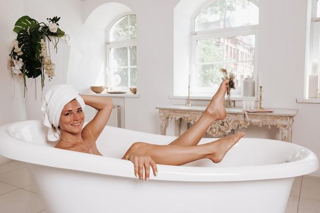 幸せな美しい女性は、自宅の熱いお風呂でリラックスして朝の時間を楽しんでいます。