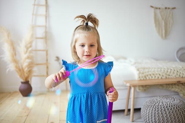 両親の寝室でシャボン玉を吹いて、屋内で楽しんでいるポニーテールの幸せな美しい女性の子供。一人で家で遊んで、自分を楽しませるかわいい青いドレスを着ている魅力的な少女