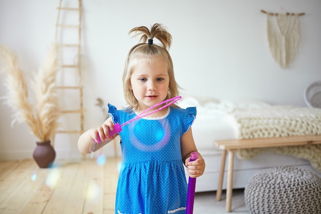 Felice bella femmina bambino con coda di cavallo divertendosi al chiuso, soffiando bolle di sapone nella camera da letto dei genitori. affascinante bambina che indossa un abito blu carino intrattenere se stessa, giocando in casa da sola
