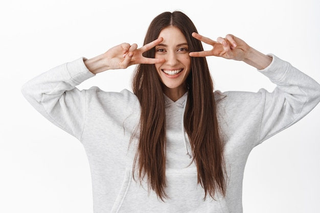 Happy beautiful female model with long healthy straight hair, showing v-sign peace gesture, disco fingers over eyes, smiling broadly, standing against white wall