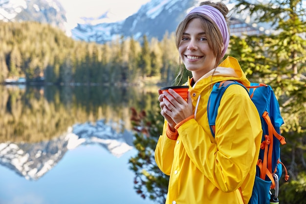 Happy beautiful female traveler spends free time in moutain resort, drinks coffee from disposable cup