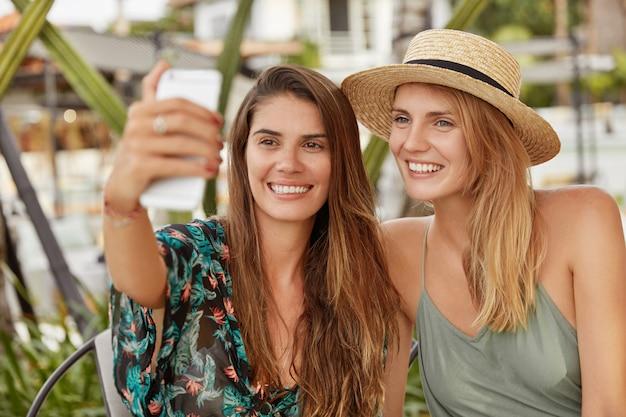 広い笑顔で幸せな美しい女性は、居心地の良いエキゾチックなカフェテリアで一緒に座っている間、自分撮りのためにポーズし、写真を作るために現代のスマートフォンを使用します。