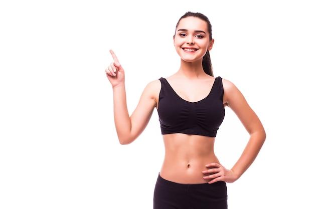Счастливая красивая женщина фитнеса в спортивной одежде указывая вверх на copyspace. отдельный на белом фоне