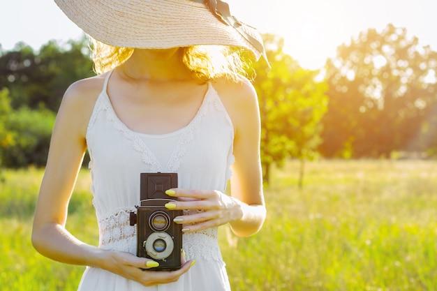 幸せな美しい楽しい女の子女性流行に敏感な摩耗麦わら帽子長い白いドレスホールド撮影古い大きな珍しい写真カメラで大きな大きな広い夏温泉日当たりの良い緑の果樹の間のライトフィールド