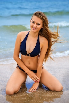 Happy beautiful girl on beach in swimsuit
