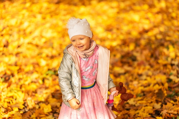Happy beautiful girl child in fashionable clothes with a toy walks in the golden park with autumn yellow foliage