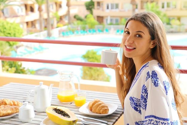 彼女の休暇のリゾートホテルで朝食を楽しんで幸せな美しい女の子