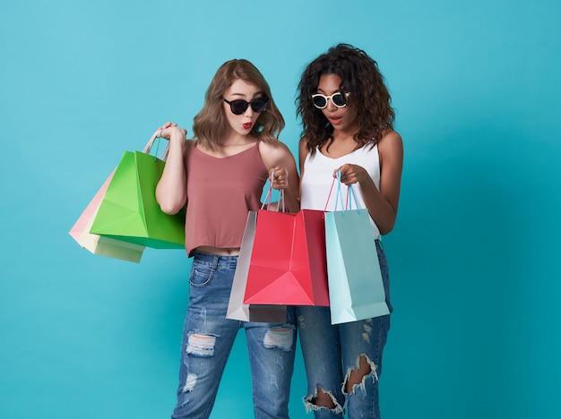 青い背景に分離された買い物袋を探して幸せな美しいガールフレンド。