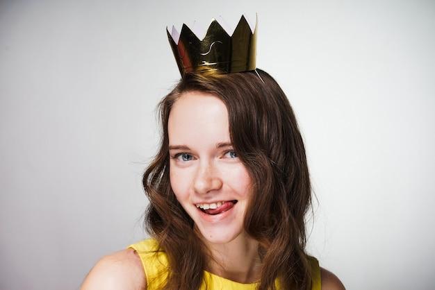 노란 드레스를 입은 행복한 아름다운 소녀는 그녀의 머리에 황금 왕관을 쓰고 있는 세계 여성의 날 휴일에 행복합니다