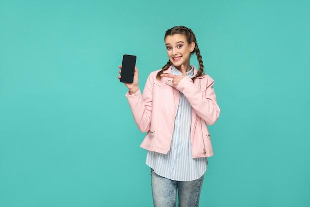 Счастливая красивая девушка в повседневном или хипстерском стиле, прическа косичка, стоя, держа и указывая на мобильный дисплей, экран с зубастой улыбкой, снимок в помещении студии, изолированный на синем или зеленом фоне