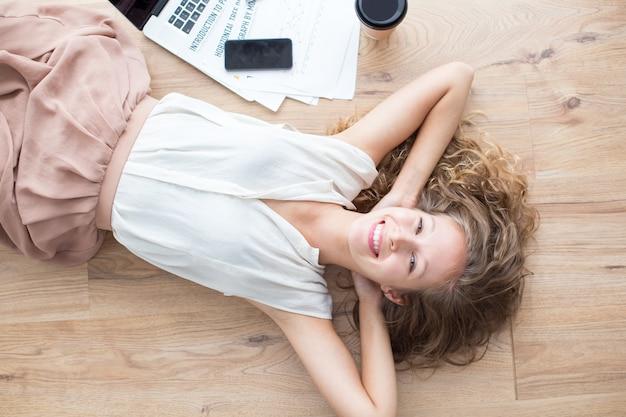 ハッピー美しい女の子は、床に横たわるとリラックス