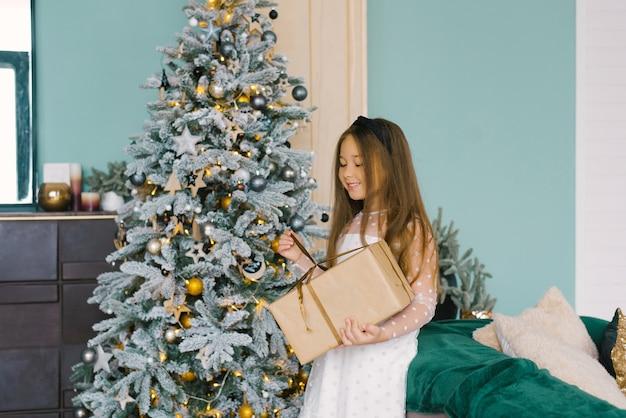 幸せな美しい少女は、お祝いのクリスマスツリーの近くに立っている間、クリスマスプレゼントを開きます